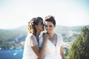 two lesbians getting married with a beautiful lake in the background
