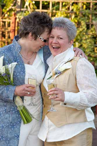 two lesbians at wedding wearing waistcoats