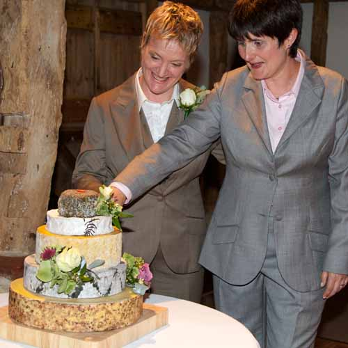 two lesbians at wedding wearing grey suits