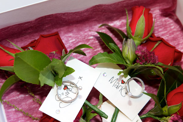 wedding rings in box with red roses