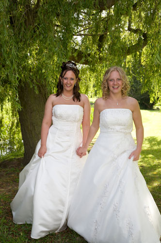 two lesbians at wedding wearing traditional ivory wedding dresses