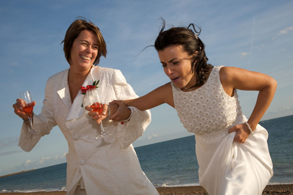two lesbians at wedding wearing cream suit and cream dress