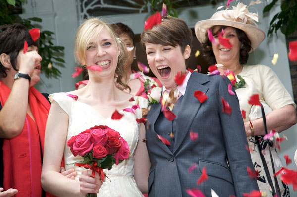 two lesbians at wedding wearing  fitting grey wedding suit and wedding dress
