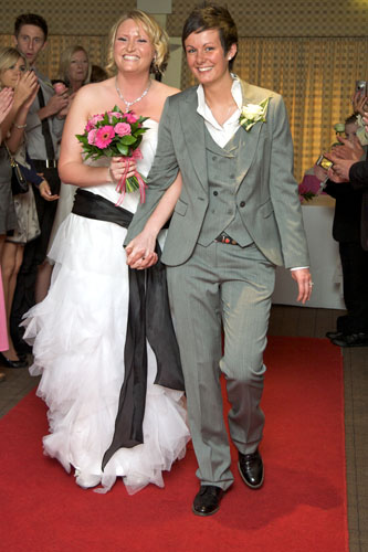 two lesbians at wedding wearing grey suit and white wedding dress