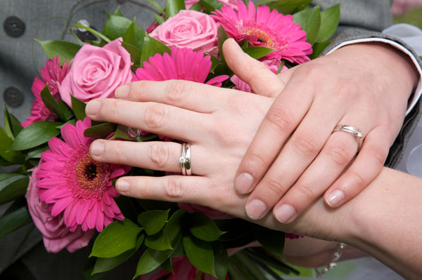 lesbian wedding rings with pink flowers in background