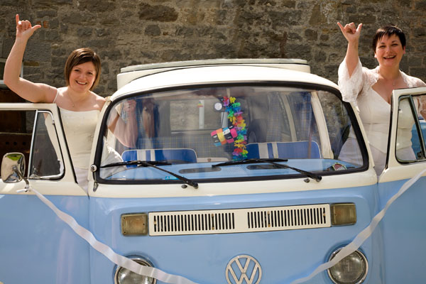 two lesbians with campervan at wedding
