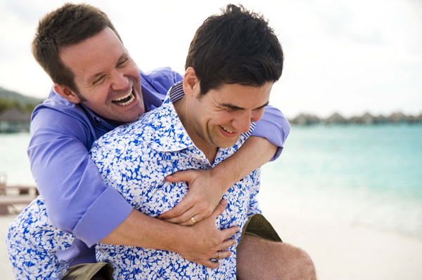 two gay men hugging on a beach at their wedding