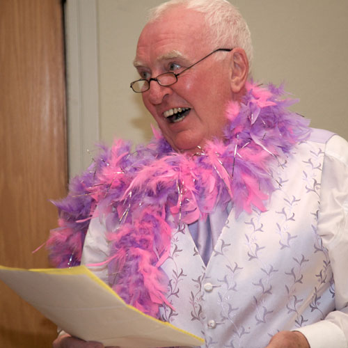 gay man wearing pink feather scarf giving wedding speech