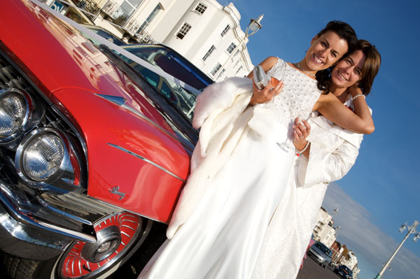 two lesbians in wedding gowns posing by red sports car