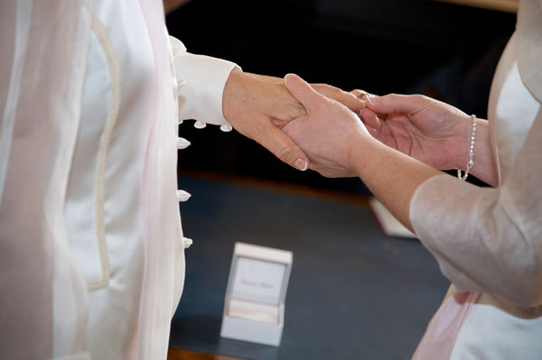 two lesbians at their wedding placing ring on finger