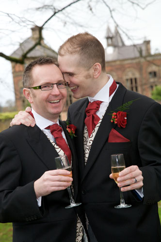 two gay grooms laughing with champagne