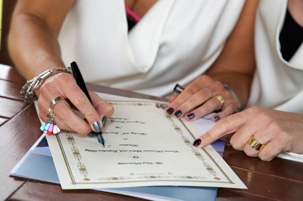 two lesbians signing marriage certificate