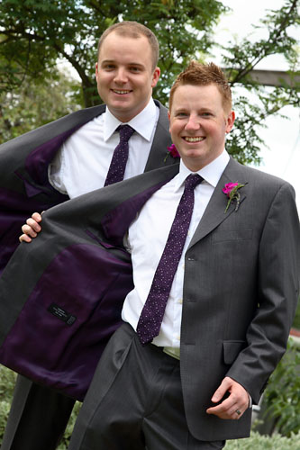 two gay grooms showing their suits