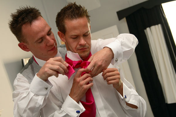 two gay grooms helping with wedding tiw