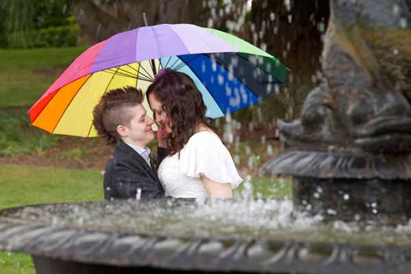 two lesbian brides with rainbow umbrella