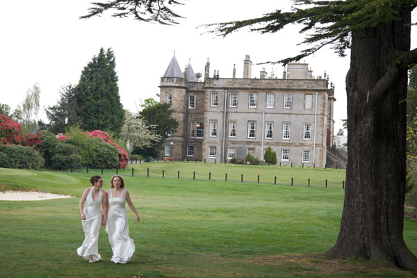 two lesbian brides walking on grass of historic venue
