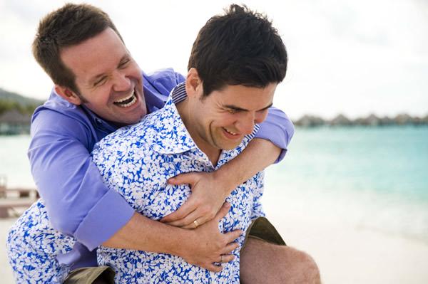 two gay men hugging on beach