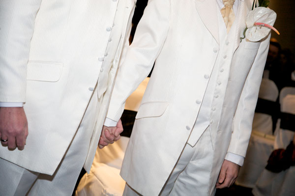 two gay grooms in white suits