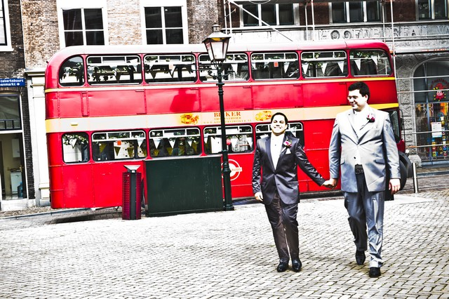 gay men at wedding with red london bus behind