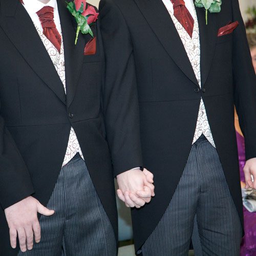 two gay men holding hands at their wedding with smart suits on
