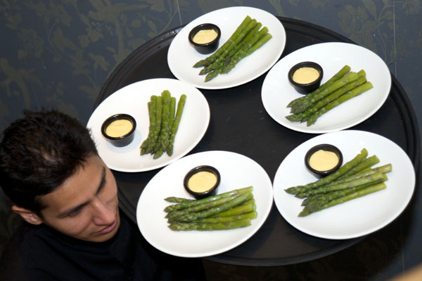 wedding waiter carrying plates of asparagus