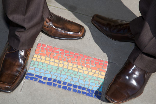two pairs of feet at gay wedding on rainbow tile