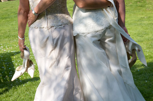 two lesbians in their wedding dresses arm in arm