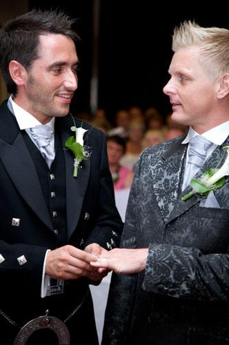 two gay men putting ring on finger civil partnership