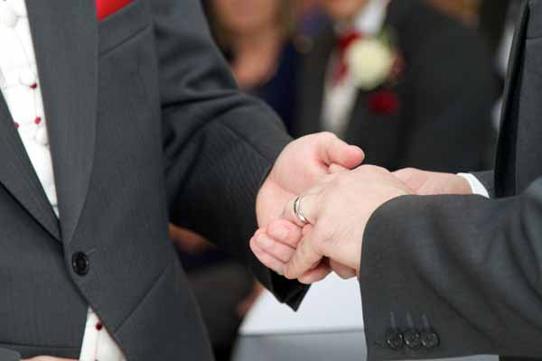 two gay grooms placing ring on fingers